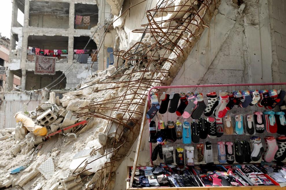 9/03/2021. Un puesto de venta de ropa cerca de los edificios dañados en Douma, al este de Damasco. - Reuters