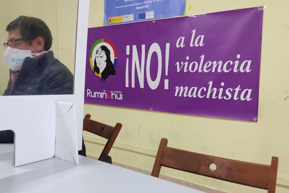 Vladimir Paspuel, presidente de la Asociación Rumiñahui, observa el teléfono móvil en una mesa donde recibe a los jóvenes de las bandas. Al fondo un cartel contra la violencia machista. - Guillermo Martínez