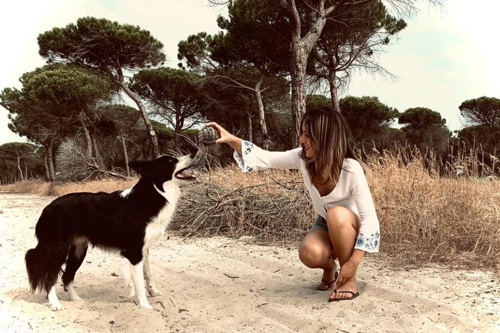 Laura juega con su perro en la playa