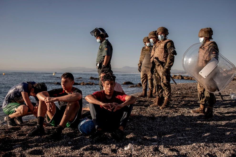 Miembros del ejército observan a un grupo de inmigrantes menores a su llegada a la playa de El Tarajal en Ceuta.