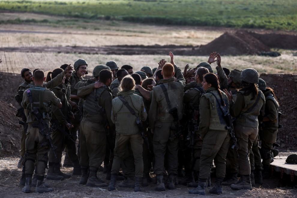 Soldados israelíes vitorean mientras se reúnen en una posición de la unidad de artillería cerca de la frontera entre Israel y la Franja de Gaza, en el lado israelí 17 de mayo de 2021.