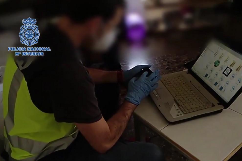 Agentes de la Policía Nacional registran los dispositivos electrónicos del pederasta, en Benidorm. - Policía Nacional