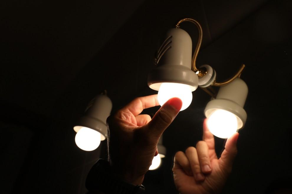 Una persona cambia la bombilla de una lámpara, el día en que el precio de la luz bate un récord histórico alcanzando los 124,45 euros por megavatio hora, a 30 de agosto de 2021, en Madrid, (España).