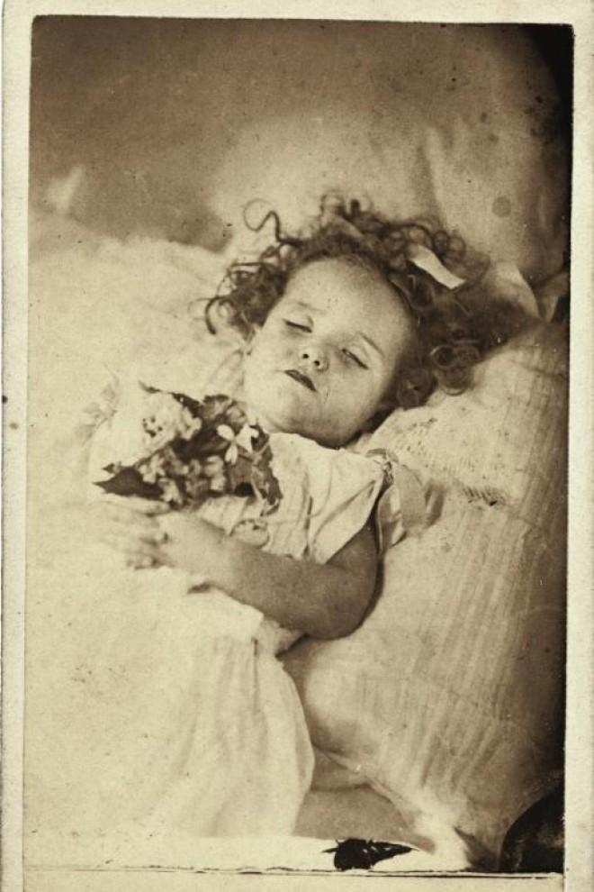 Retrato de una niña fallecida con un vestido y un ramo de flores entre las manos. - Cedida