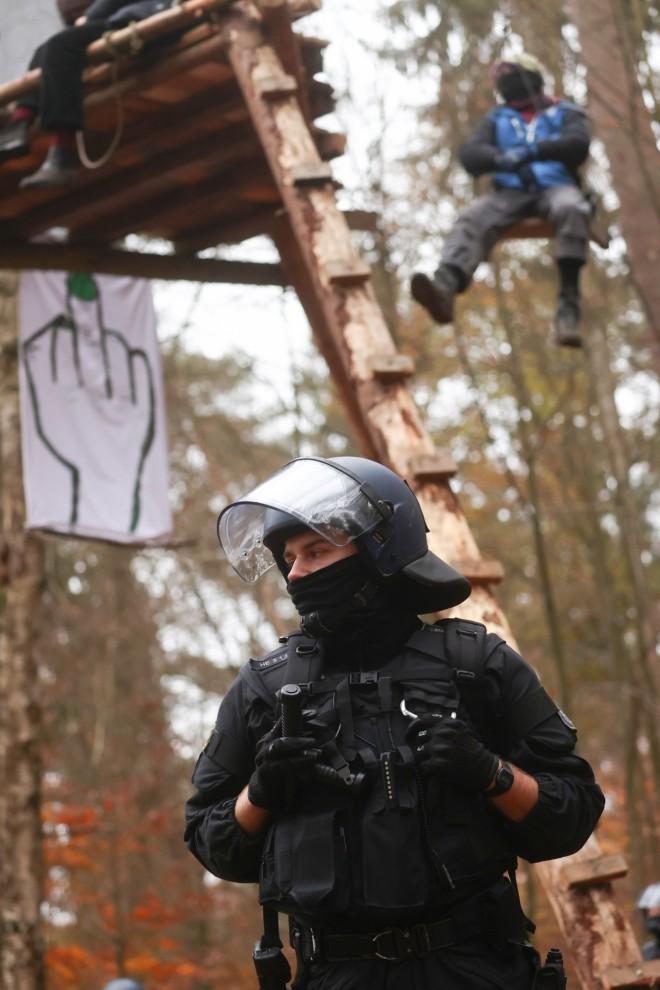 Un oficial de policía en la protesta contra la extensión de la autopista A49. Detrás un activista encaramado a los árboles.