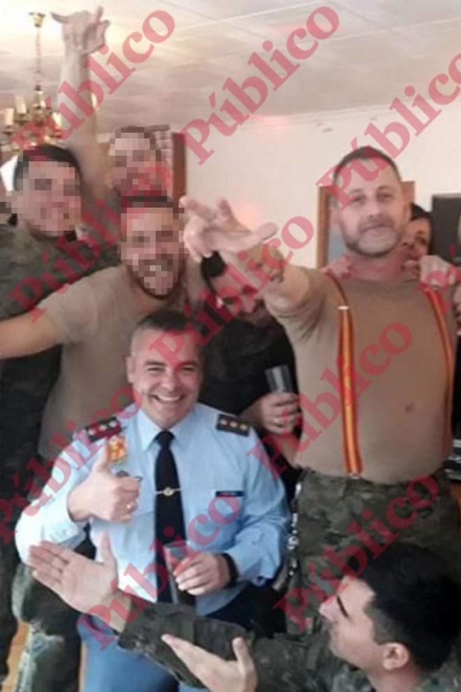 El capitán Meroño lleva corbata y el cabo Díaz Pérez, con tirantes, hace el saludo nazi.