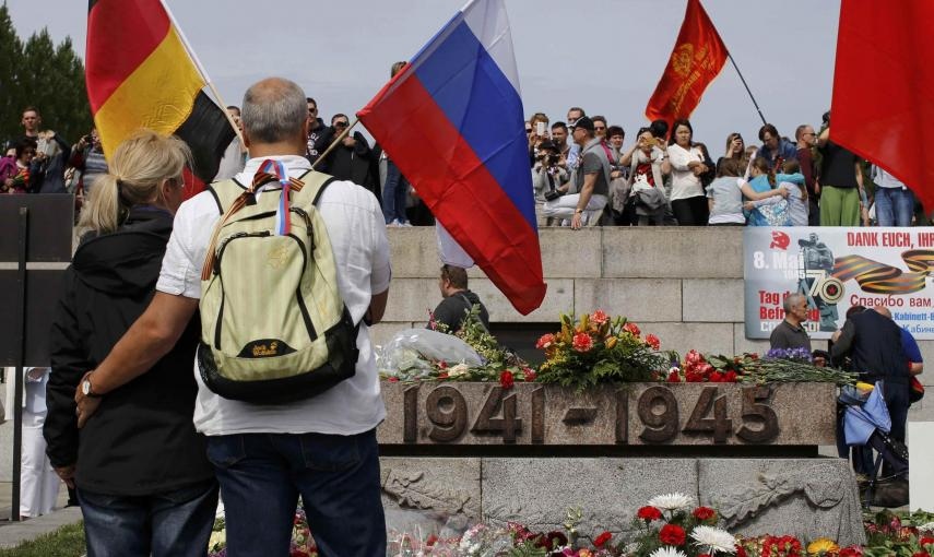 A couple holds a German and a Russian flag during celebrations to mark Victory Day, at the Soviet War Memorial in Treptower Park in Berlin, Germany, May 9, 2015. REUTERS/Fabrizio Bensch