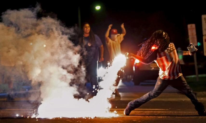 Edward Crawford devuelve un bote de gas lacrimógeno disparado por la policía, que intentaba dispersar la protesta en Ferguson, Mossouri, Estados Unidos./ REUTERS/Robert Cohen/St. Louis Post-Dispatch/Handout