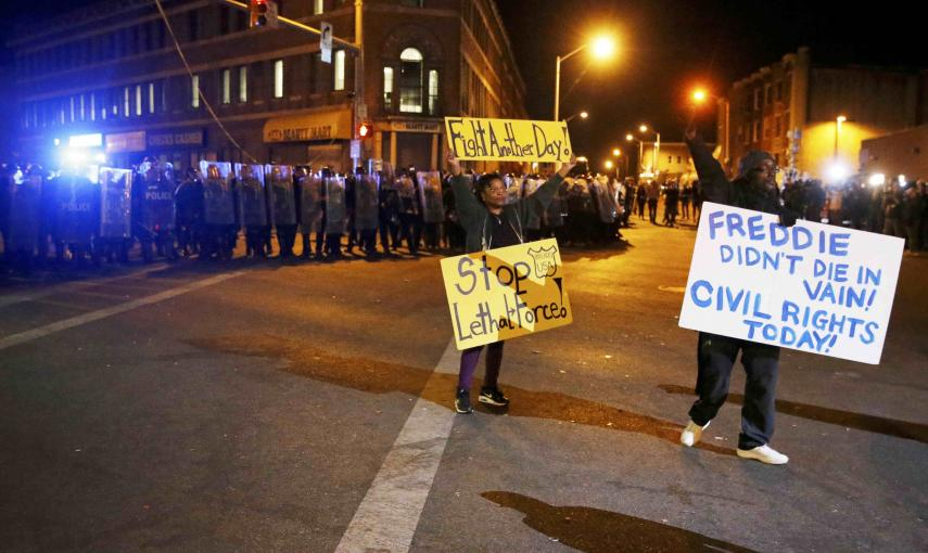 Protesters hold up signs in front of a line of police in Baltimore, Maryland. REUTERS/Jim Bourg