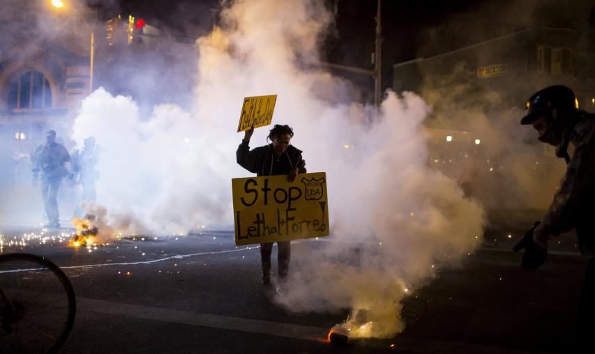 A protester holds a sign as clouds of smoke and crowd control agents rise, shortly after the deadline for a city-wide curfew passed in Baltimore, Maryland. REUTERS/Eric Thayer