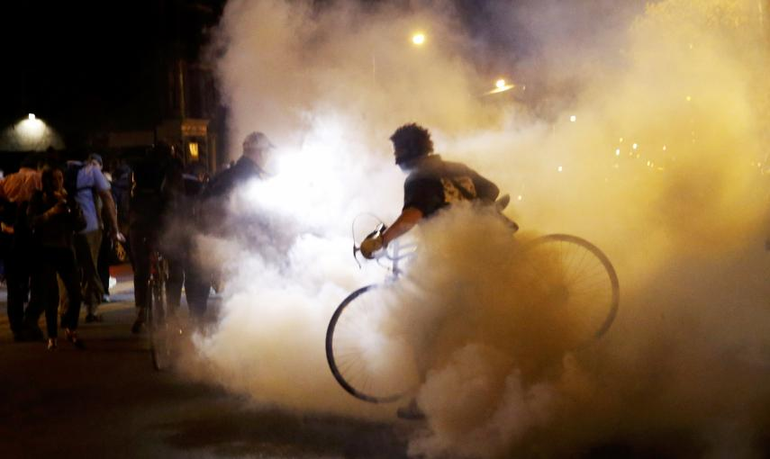 A protester moves his bicycle as clouds of smoke and crowd control agents rise shortly after the deadline for a city-wide curfew passed in Baltimore. REUTERS/Shannon Stapleton