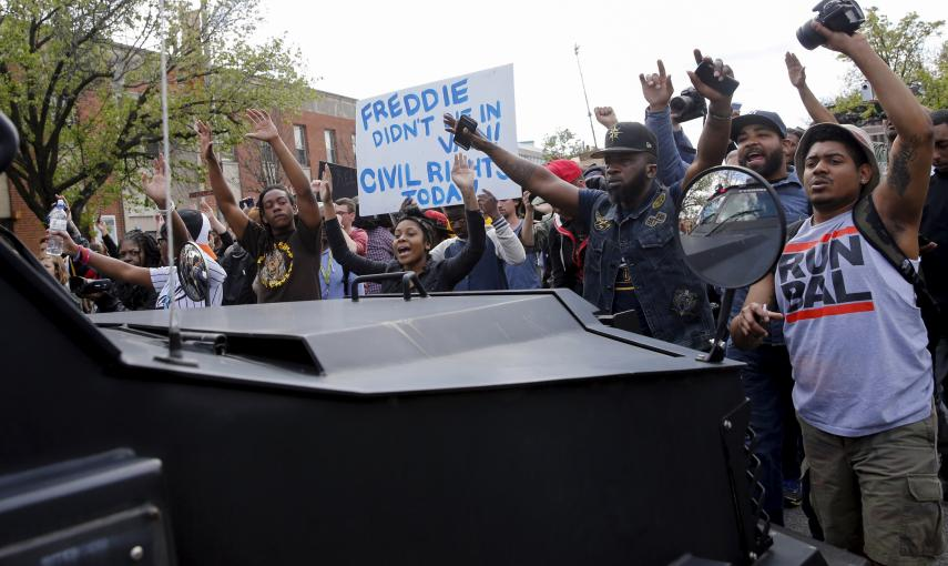 Demonstrators march in front of a Baltimore police vehicle down Pennsylvania Avenue, a day after it was looted and set ablaze in protest for the death of 25-year-old black man Freddie Gray who died in police custody in Baltimore. REUTERS/Shannon Stapleton