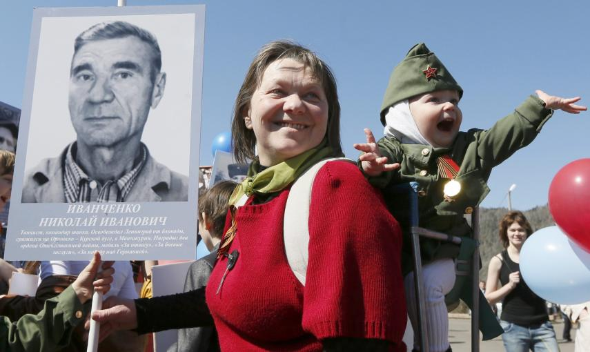 A woman with a child holds picture of World War Two soldier as she takes part in the Immortal Regiment march during the Victory Day celebrations in Divnogorsk. REUTERS/Ilya Naymushin