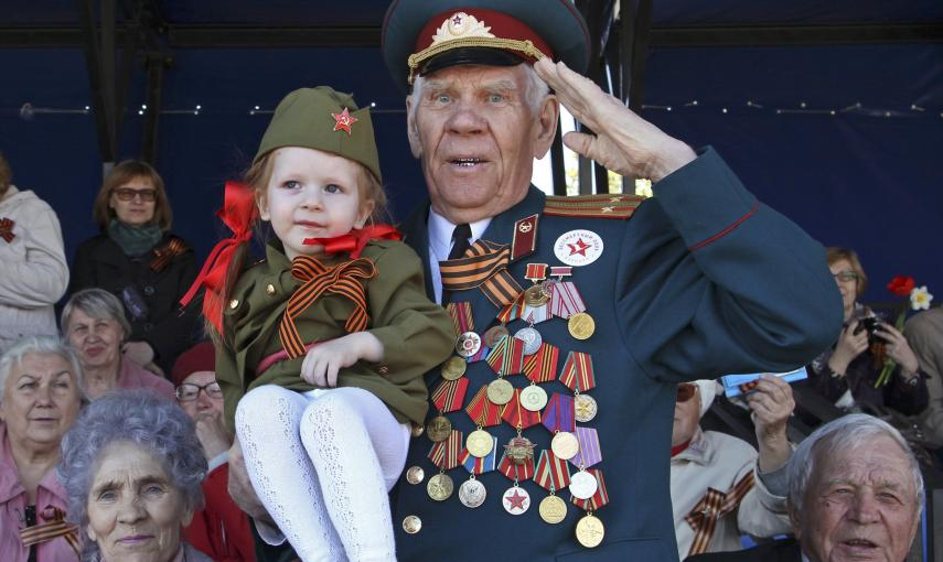 A World War Two veteran salutes as he watches the Victory Day parade in Barnaul. REUTERS/Andrei Kasprishin