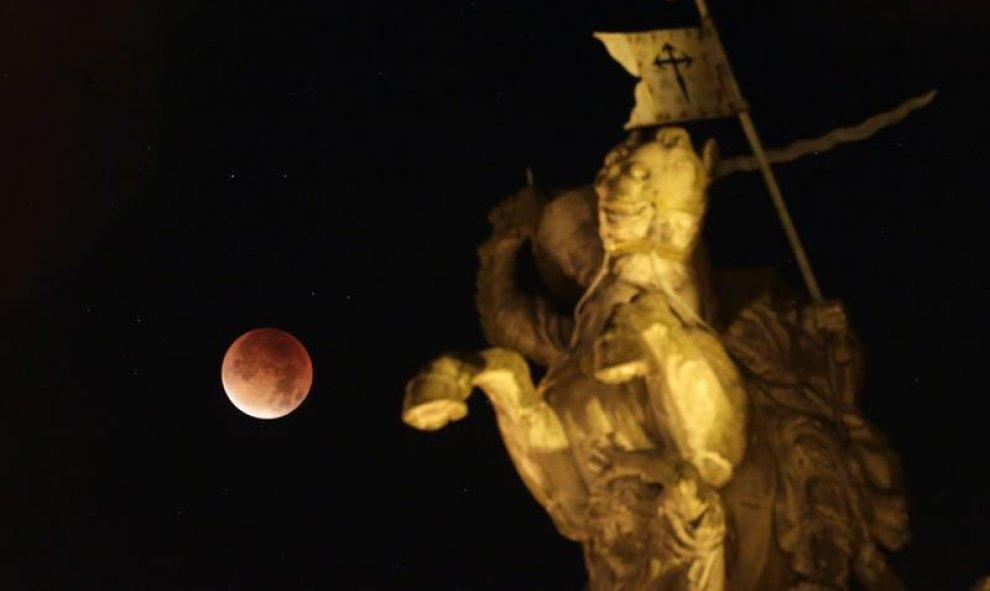 Fotografía de un eclipse total de luna visto junto a una escultura del apóstol Santiago a caballo en la madrugada de hoy, lunes 28 de septiembre de 2015, cerca al ayuntamiento de Santiago de Compostela (España). EFE/Lavandeira jr