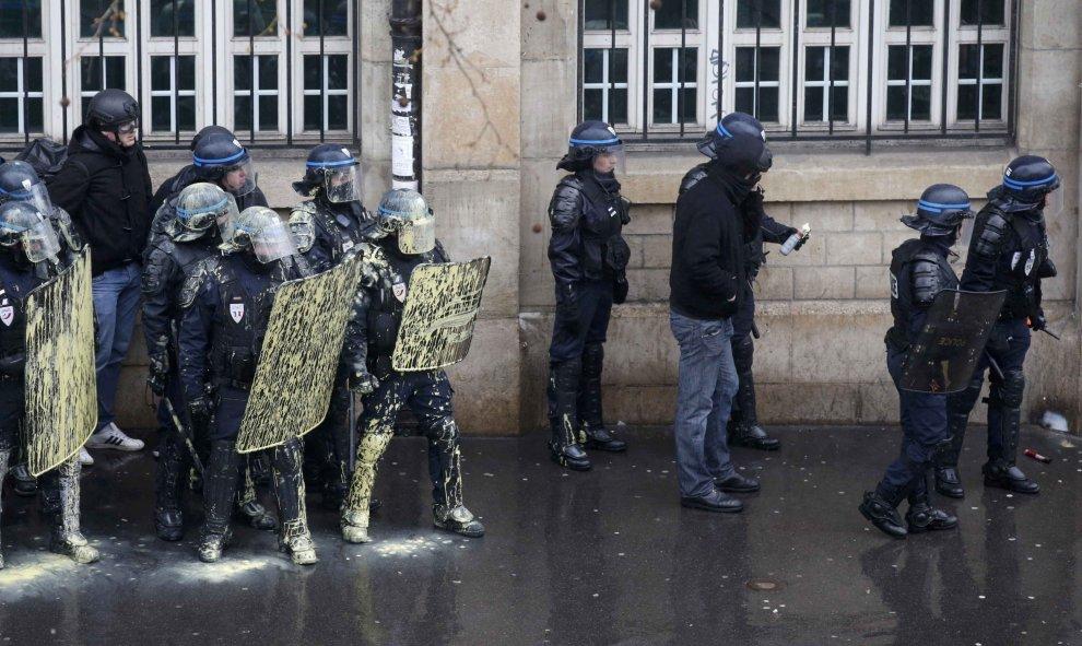 La policía antidisturbios francesa protegerse detrás de escudos durante una manifestación de estudiantes de instituto y universitarios franceses en contra de la propuesta de la legislación laboral francés en París. REUTERS