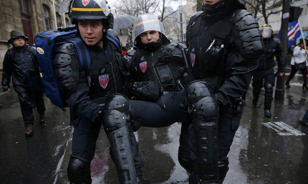 Los antidisturbios sacan a un compañero de la manifestación en París, durante los enfrentamientos con los estudiantes y obreros./REUTERS