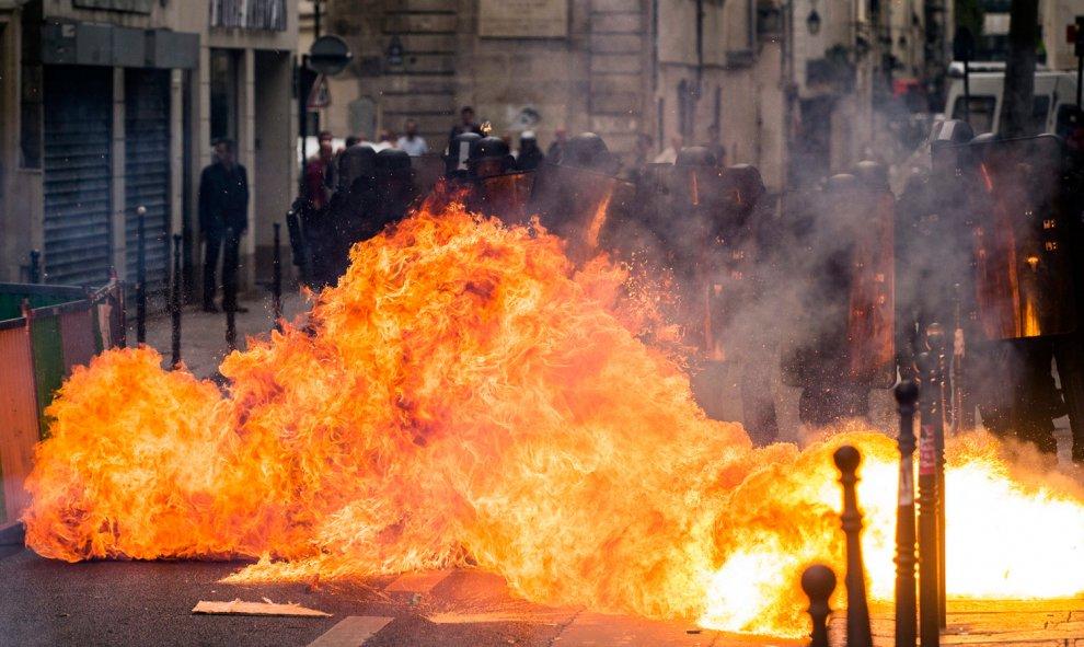 Un cóctel mólotov explota al lado de varios policías durante una manifestación contra la nueva reforma laboral en París.- EFE/Etienne Laurent