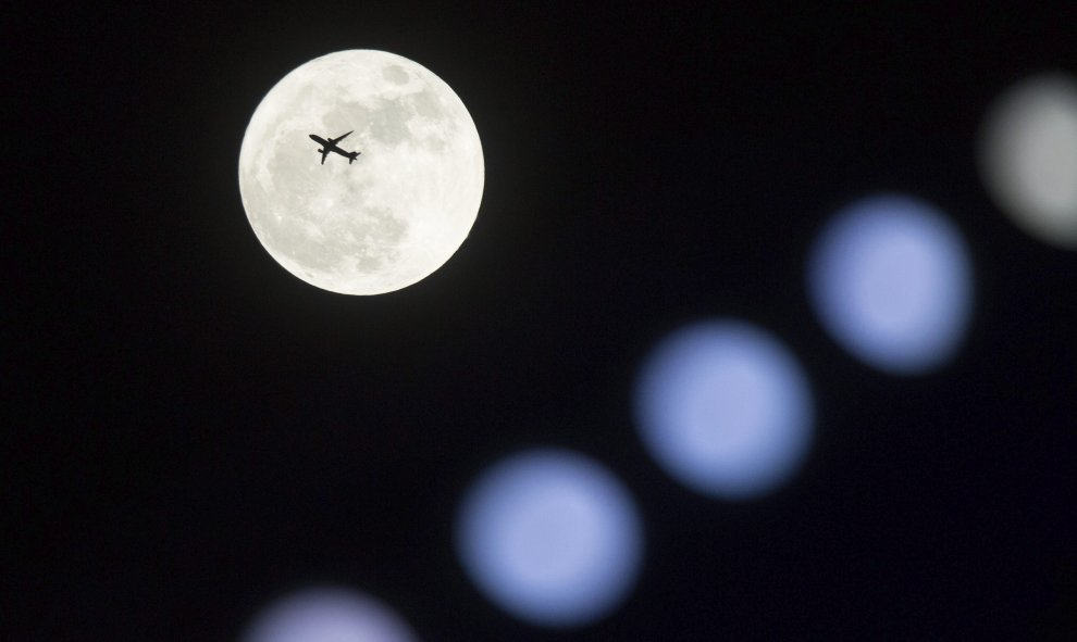 Un avión vuela frente a la superluna en Hong Kong (China). EFE/Jerome Favre