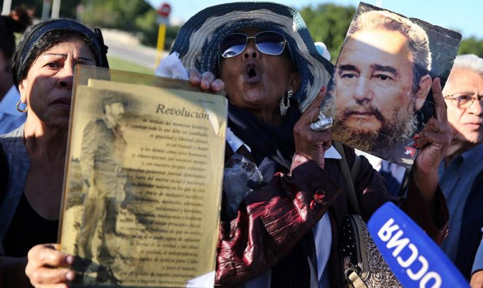Dos mujeres muestran retratos del fallecido líder cubano Fidel Castro, durante un homenaje póstumo en la Plaza de la Revolución de La Habana (Cuba). EFE