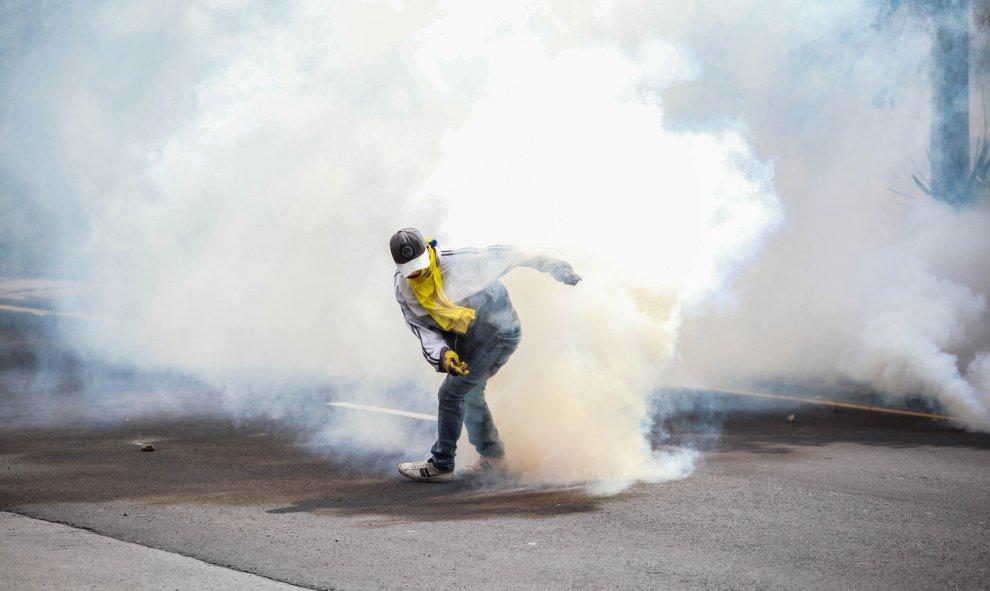 Un joven con una máscara rodeado de gas lacrimógeno. / Europa Press -  Juan Diego Montenegro