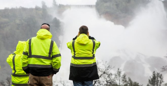 California Department of Water Resources personnel monitor water flowing through a damaged spillway on the Oroville Dam in Oroville, California