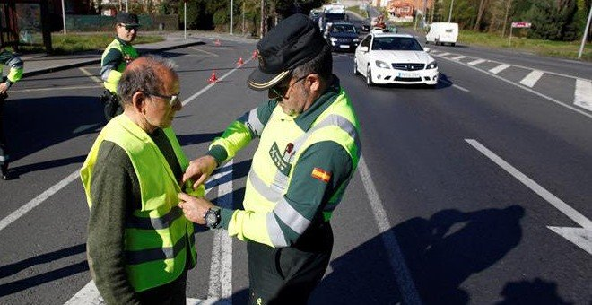 Un guardia civil coloca un chaleco reflectante a un peatón. / EFE