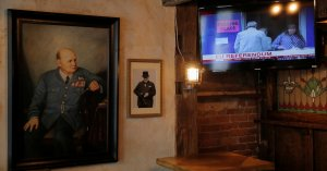 A painting of former British Prime Minister Winston Churchill hangs beside a television broadcasting Brexit polling at The Churchill Tavern, a British themed bar, on the day Britain votes whether or not to remain in the European Union, in the Manhattan bo
