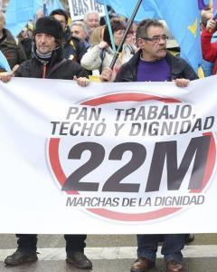 Dos participantes en las Marchas por la Dignidad tras una de las pancartas en la Plaza de Colón. EFE/Ballesteros