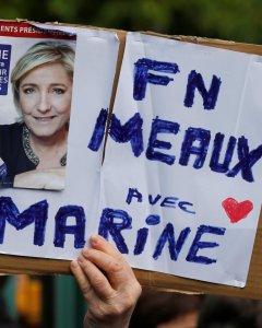 Un seguidor del Frente Nacional, sujeta una pancarta con la imagen de Marine Le Pen. REUTERS/Pascal Rossignol