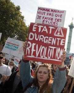 Una manifestante pone un cartel que reza 'Mamá, Macron no quiere que estudie. Revolución urgente', esta tarde, en la marcha convocada por la Francia Insumisa de Mélenchon contra la reforma laboral del Gobierno francés. REUTERS/Philippe Wojazer