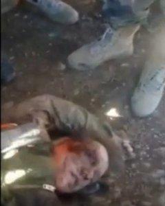 El cuerpo sin vida de un piloto ruso de un avión de guerra derribado por Turquía , rodeado de miembros del grupo rebelde sirio. REUTERS