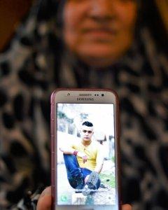 Fadilih Khalaf muestra una foto de su hijo Abdalah, que trabaja como camarero en España. /ANDREA OLEA