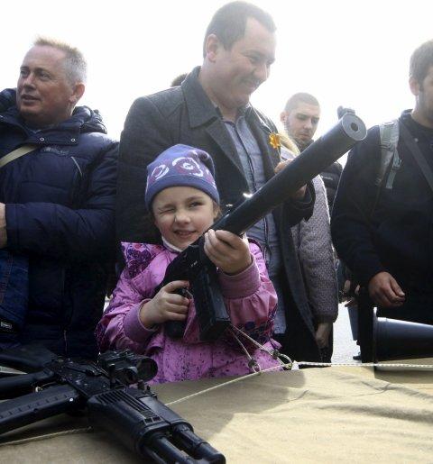 Un pequeña coge un arma para inspeccionarla durante la celebración del Día de Rusia, en Sevastopol, Crimea. REUTERS/Pavel Rebrov