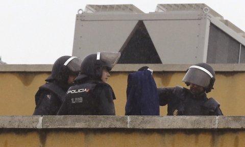 Efectivos de la Policía Nacional permanecen en la azotea del Centro de Internamiento de Extranjeros (CIE) de Aluche, en Madrid, donde anoche se encerraron unos cuarenta inmigrantes. EFE/Paco Campos