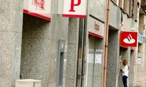 Una mujer usa un cajero automático en una oficina del Banco Santander junto a una sucursal del Banco Popular. REUTERS/Albert Gea