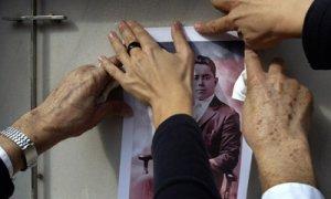 Los familiares de Emilio Silva Faba colocan su foto en el nicho del cementerio en 2000.