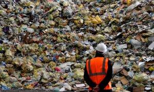 Un operario observa parte de los residuos prensados en una planta de reciclaje. /AFP