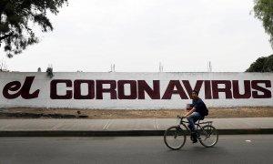 Un ciudadano pedalea con su bicicleta junto a un muro con una pintada que hace referencia al coronavirus. REUTERS/Carlos Jasso