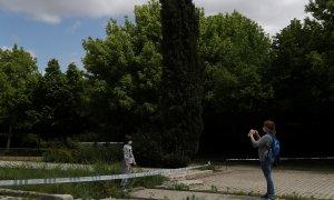 Una mujer realiza una foto a su hija en un parque clausurado de Madrid./ REUTERS