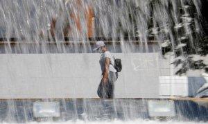 Una mujer pasa ante una fuente en Córdoba que este fin de semana registra altas temperaturas con aviso naranja decretado por la Agencia Estatal de Meteorología (Aemet). EFE/Salas