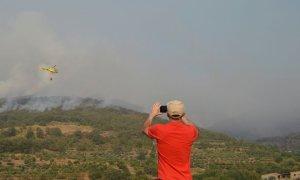 Un vecino de la localidad de Aldeanueva de la Vera (Cáceres) otografía los trabajos de extinción del incendio forestal declarado en Cabezuela del Valle, en la comarca cacereña del Valle del Jerte. / EFE/ Eduardo Palomo