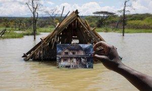 Un hombre sostiene una foto que muestra una estructura antes de que se sumergiera bajo el agua en aumento debido a las inundaciones en Kenia. REUTERS/Baz Ratner