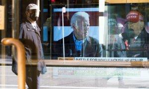 Un hombre pasa junto a un escaparate en Nueva York con un informativo sobre la disputa electoral entre Biden y Trump.