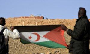 Fotografía de archivo de dos hombres sujetando la bandera del Frente Polisario en el Sáhara.