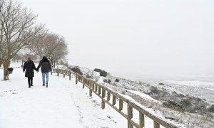 Una pareja camina por la nieve en la localidad madrileña de Los Santos de la Humosa.