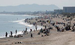 Cientos de personas pasean y toman en sol en las playas de la Dehesa de El Saler, en València, durante el Sábado Santo.