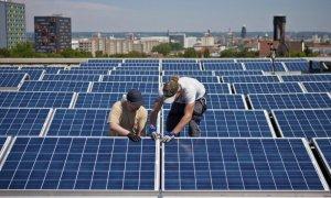 Dos operarios instalan paneles solares en el tejado de un edificios.