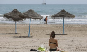 Una mujer toma el sol en una playa de Valencia.