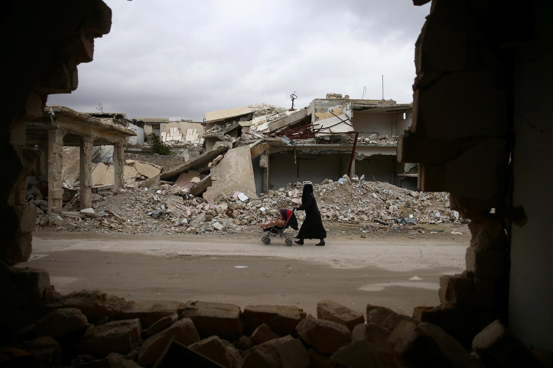 Una mujer pasea con su bebé por las ruinas de la ciudad sitiada de Douma, al este de Damasco. - REUTERS